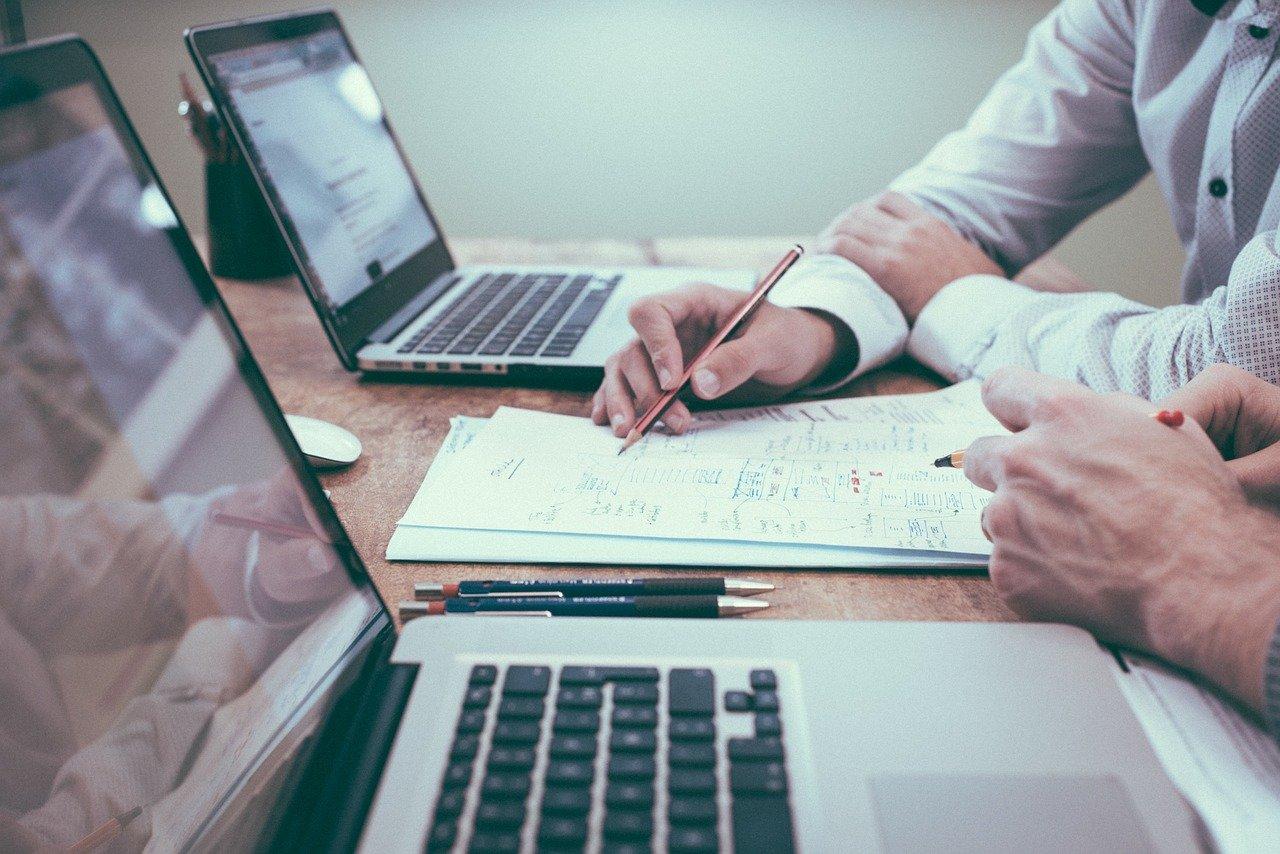Zwei Personen vor Laptops, notieren sich etwas auf Papier